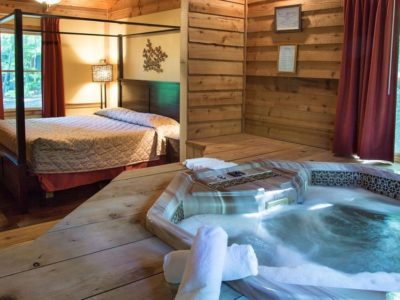 cabin interior with bed and hot tub